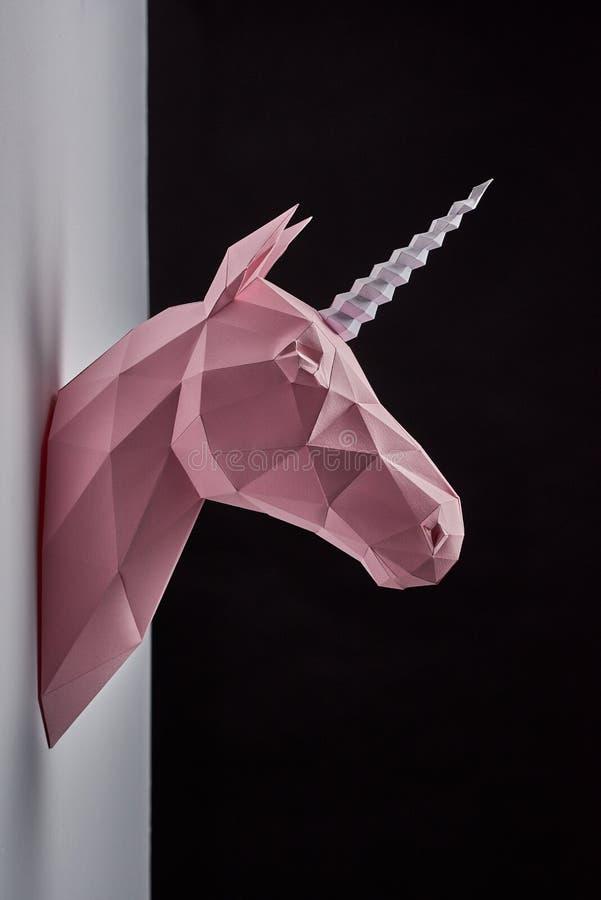 El polvo rosado coloreó la ejecución del perfil de la cabeza del ` s del unicornio en la pared del contraste imagenes de archivo