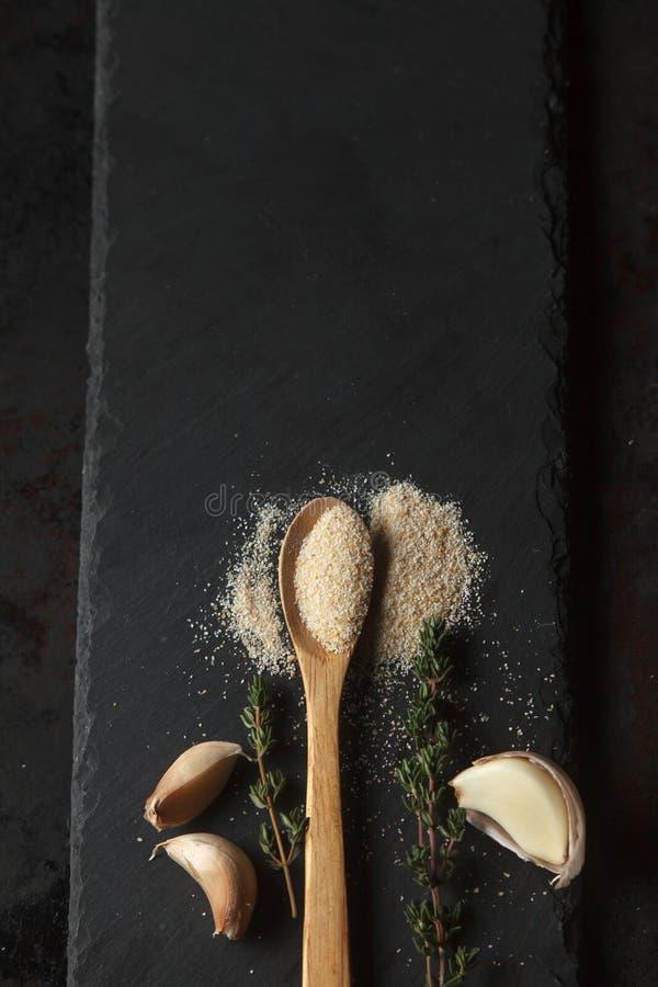 El polvo y los clavos del ajo en pizarra negra suben fotografía de archivo libre de regalías