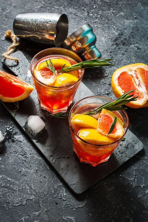 El pomelo y el romero atrapan el cóctel, restaurando la bebida con hielo imágenes de archivo libres de regalías