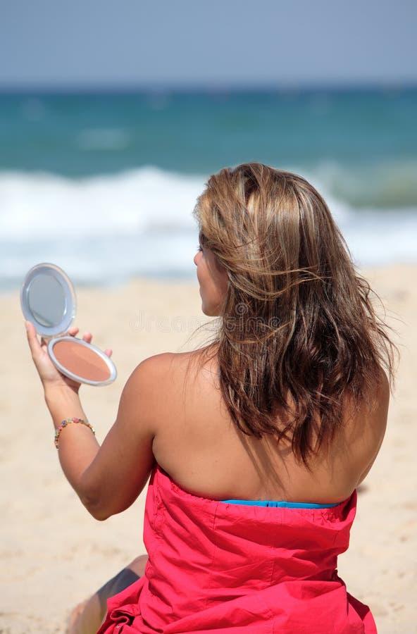 El poner bronceado joven de la mujer compone encendido mientras que en la playa fotos de archivo