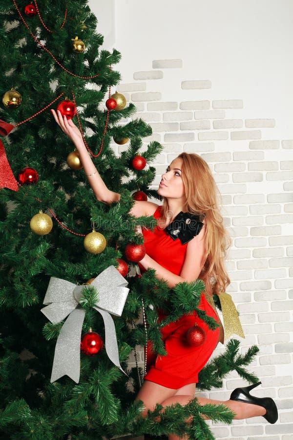 El poner de la mujer bolas en el árbol de navidad imagen de archivo libre de regalías