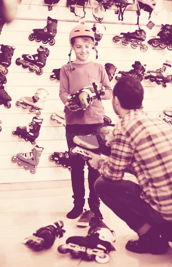 El poner masculino del vendedor patina sobre ruedas en cliente del muchacho en stor de los deportes imagen de archivo libre de regalías