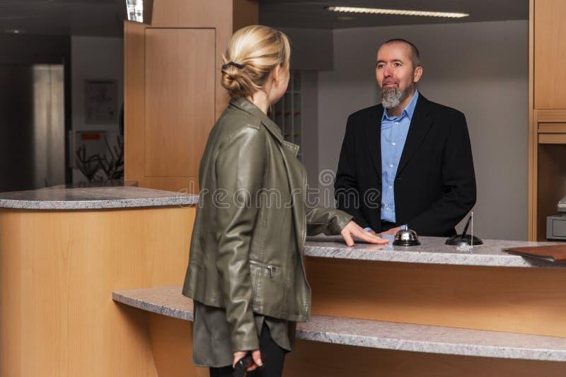 El portero en un hotel smilling a una huésped femenina fotos de archivo