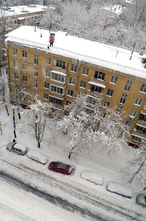 El portero limpia nieve del tejado después de nevadas en Moscú Rusia foto de archivo