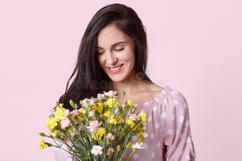 El positivo de la mujer europea joven con el pelo oscuro, sostiene el ramo bonito, sonríe suavemente, lleva la ropa de moda del l fotografía de archivo libre de regalías