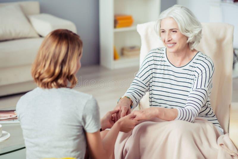 El positivo envejeció a la mujer que llevaba a cabo las manos de su nieta fotos de archivo libres de regalías