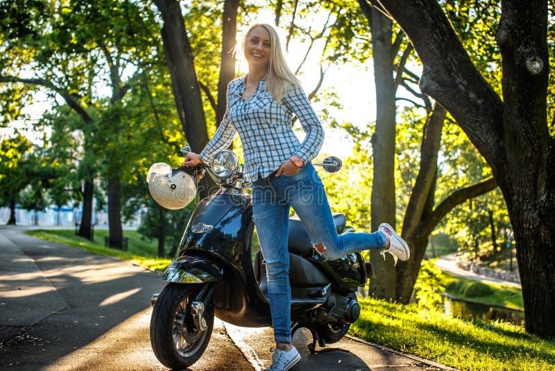 El possing femenino rubio en la vespa del moto fotos de archivo libres de regalías