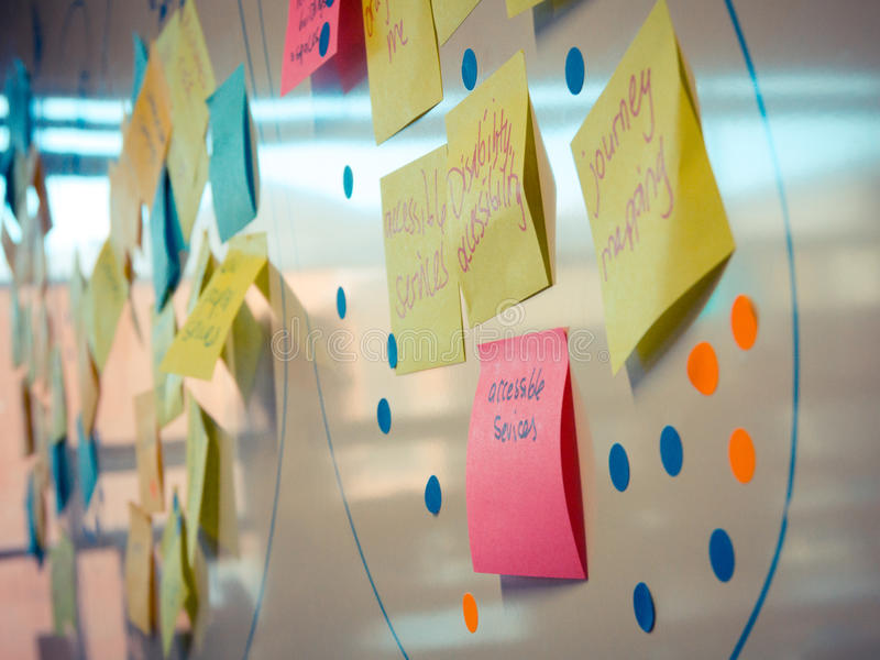 El post-it de Whiteboard coloreado observa concepto del trabajo en equipo fotos de archivo