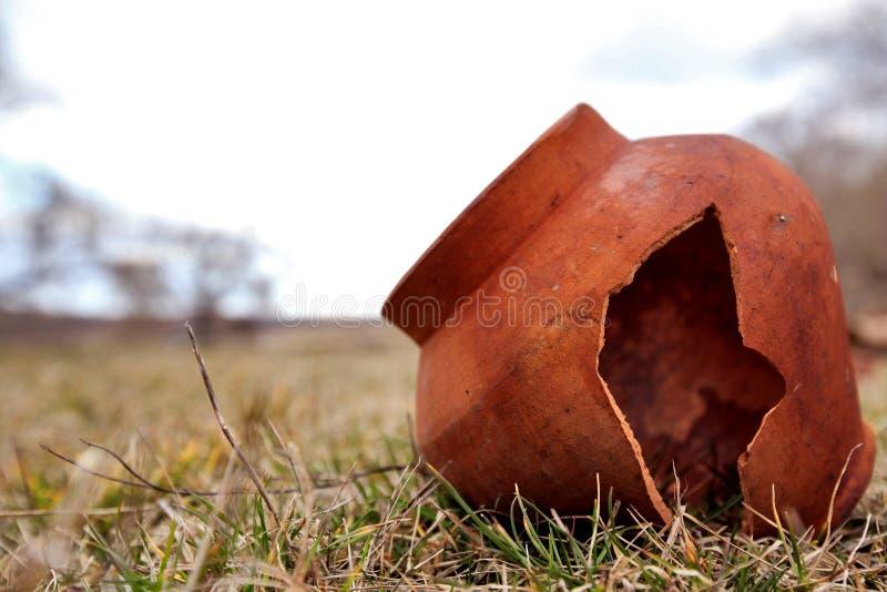 El pote de arcilla antiguo está partido en el campo Histórico de la teja abandonado El pote de arcilla está quebrado imagenes de archivo