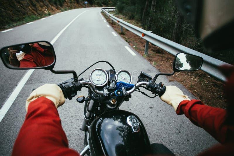 El POV tiró del hombre que conducía la motocicleta en el camino imágenes de archivo libres de regalías