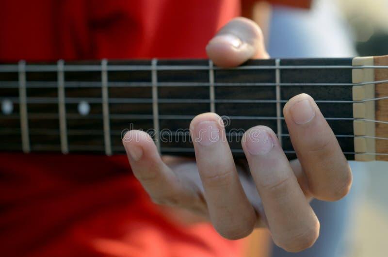 El practicar en tocar la guitarra Ciérrese para arriba de la mano del hombre que toca la guitarra foto de archivo libre de regalías