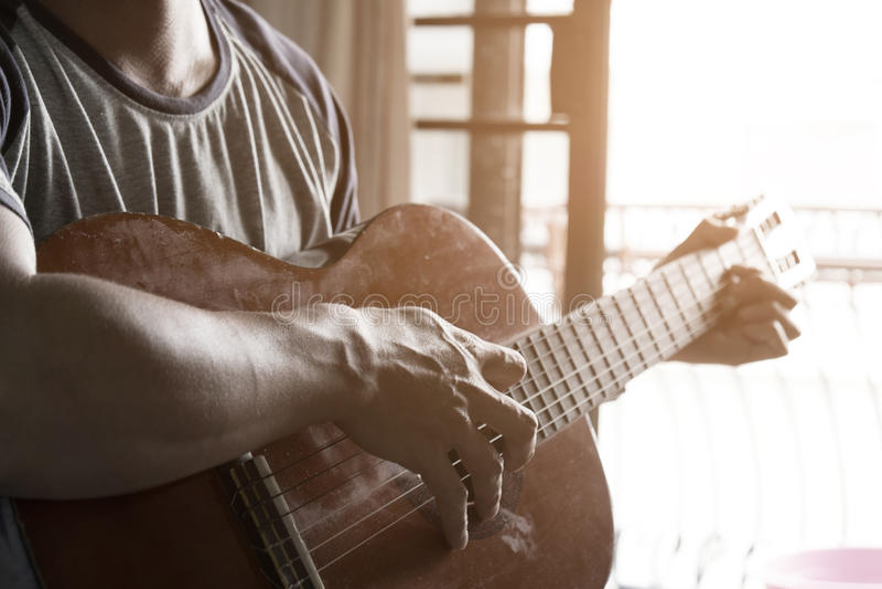 El practicar en tocar la guitarra Hombres jovenes hermosos que tocan la guitarra imagen de archivo libre de regalías