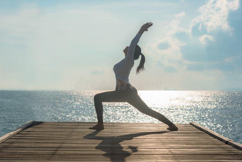 El practicar equilibrado forma de vida sana de la bola de la yoga de la mujer medita y energía en el puente por mañana la costa foto de archivo