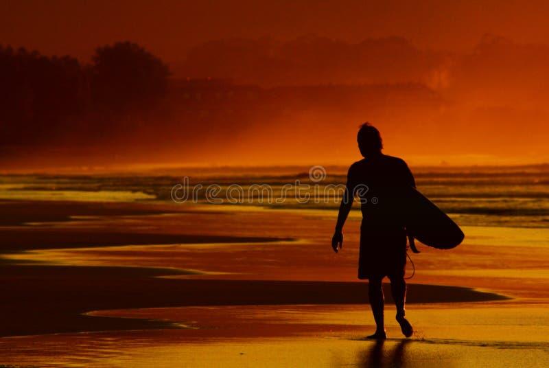 El practicar surf de la puesta del sol foto de archivo libre de regalías