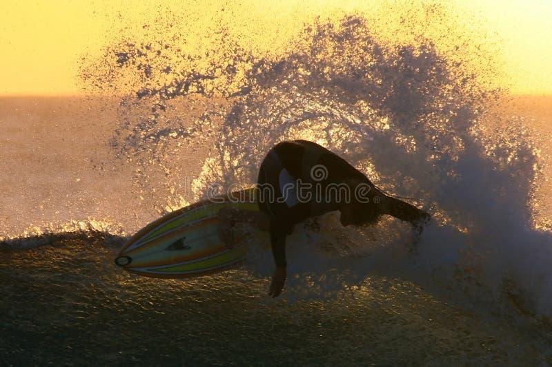 El practicar surf de la puesta del sol imágenes de archivo libres de regalías