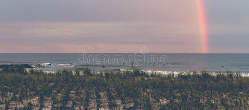 El practicar surf debajo de un arco iris en la oscuridad imágenes de archivo libres de regalías