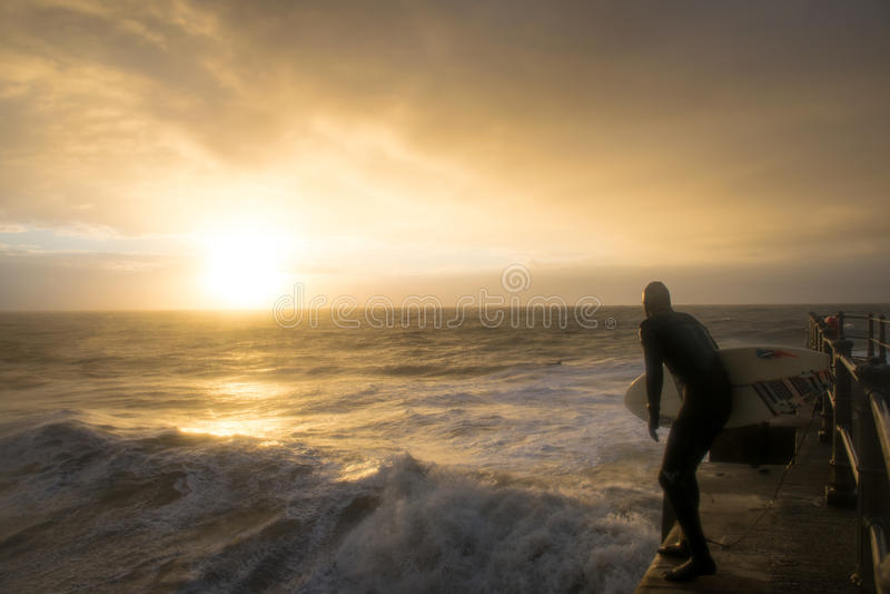 El practicar surf del brazo del puerto en la salida del sol foto de archivo libre de regalías