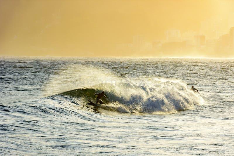 El practicar surf durante la puesta del sol del verano imágenes de archivo libres de regalías