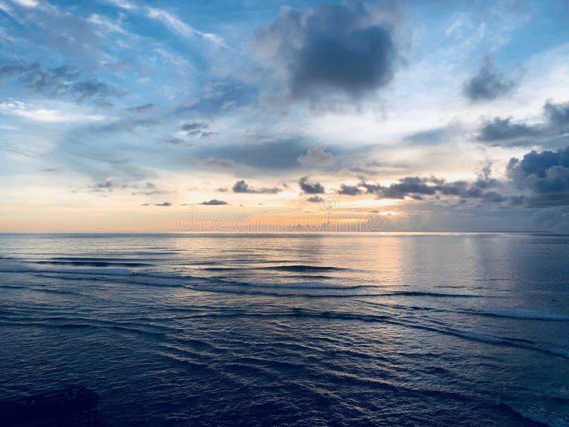 El practicar surf en Bali en la puesta del sol imagen de archivo libre de regalías