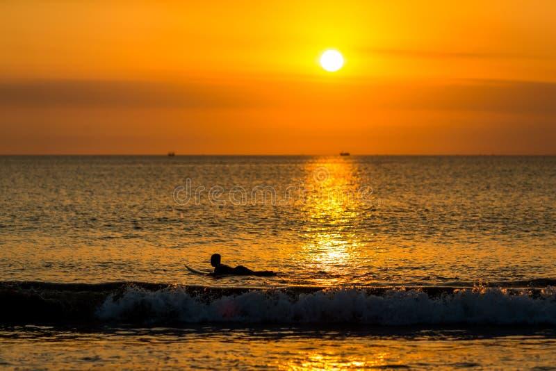 El practicar surf en la puesta del sol foto de archivo libre de regalías