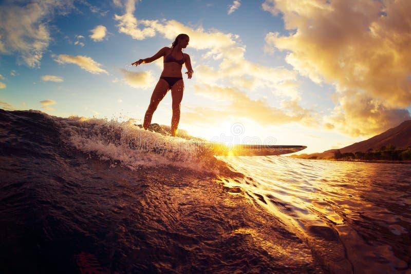 El practicar surf en la puesta del sol foto de archivo
