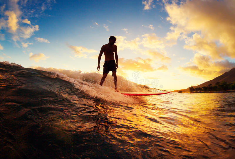 El practicar surf en la puesta del sol imagenes de archivo