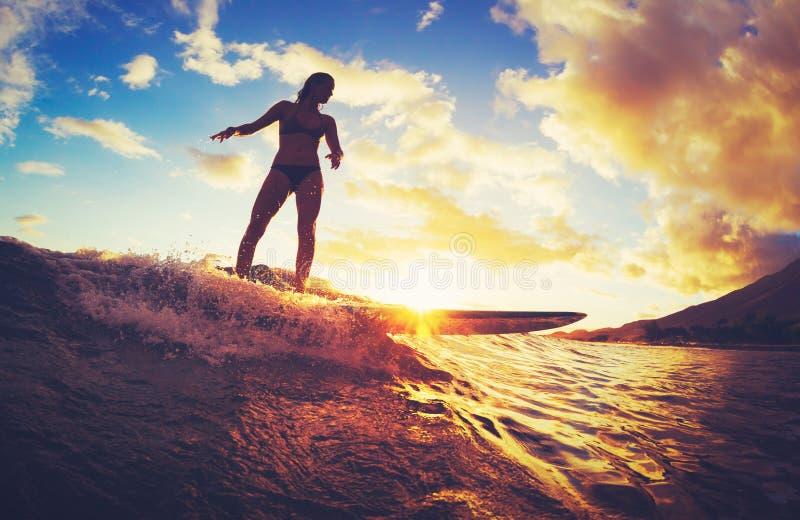 El practicar surf en la puesta del sol fotografía de archivo libre de regalías
