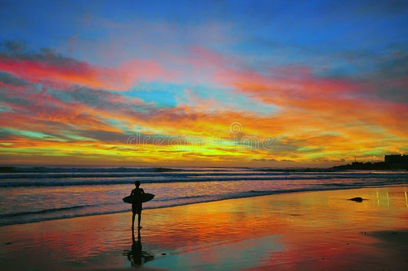 El practicar surf en puesta del sol imágenes de archivo libres de regalías