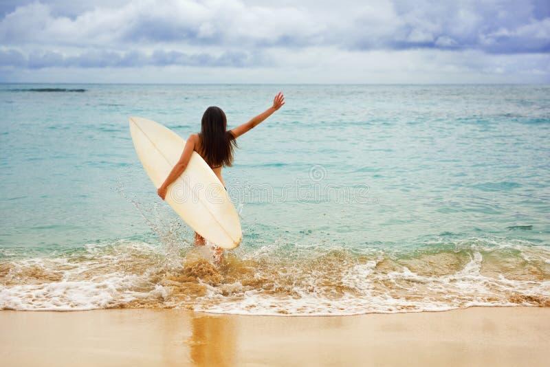 El practicar surf que va alegre feliz de la muchacha de la persona que practica surf en la playa imagenes de archivo