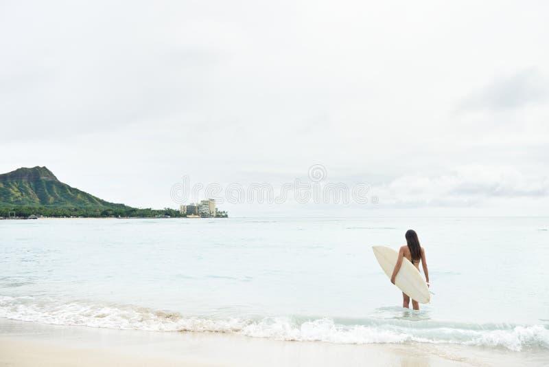El practicar surf que va de la muchacha de la persona que practica surf en la playa Hawaii de Waikiki fotografía de archivo