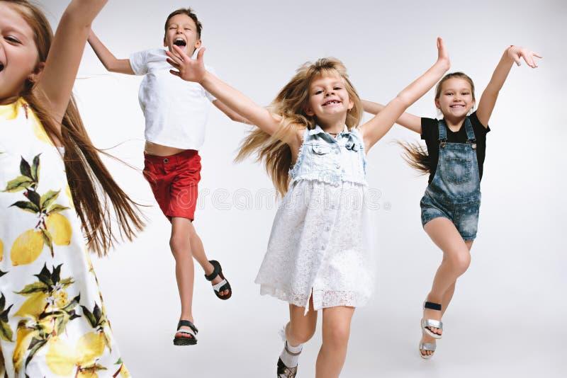 El preescolar lindo de la moda del grupo embroma a los amigos que presentan junto y que miran el fondo blanco de la cámara imágenes de archivo libres de regalías