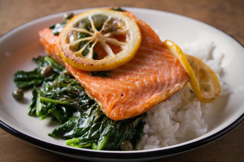 El prendedero de color salmón con arroz y la espinaca adornan filete de pescados Salmones del limón en la placa blanca en fondo d fotografía de archivo libre de regalías