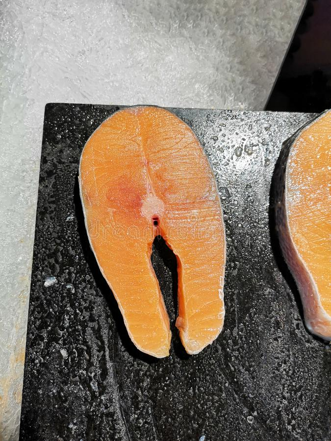 El prendedero de color salmón tiene un color anaranjado fresco, cortado en una tajadera de madera para cocinar Dentro de la cocin fotografía de archivo libre de regalías