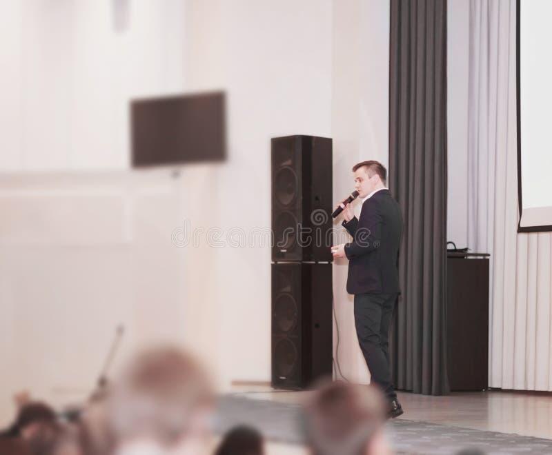 El Presidente dirige el negocio de la conferencia que se coloca delante de una pantalla blanca grande en la etapa en la conferenc imagen de archivo