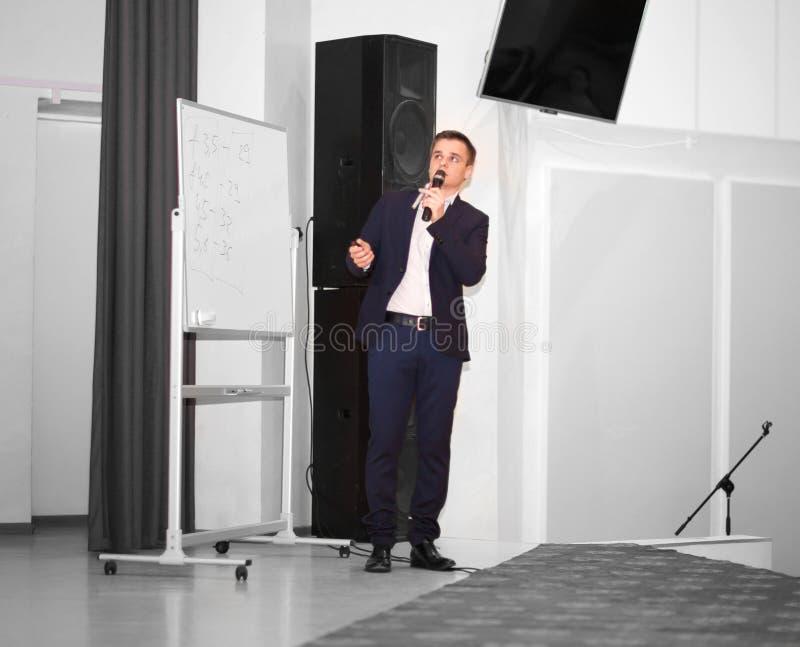 El Presidente dirige el negocio de la conferencia que se coloca delante de una pantalla blanca grande en la etapa en la conferenc fotografía de archivo