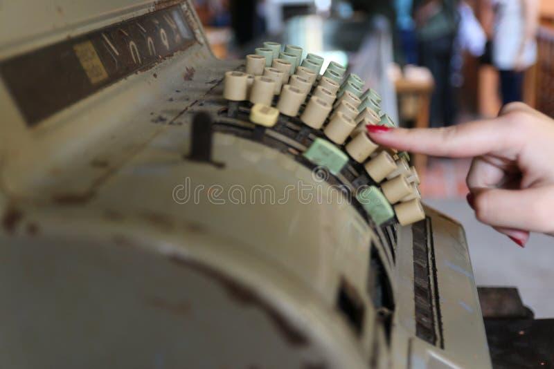 El presionado a mano de la mujer un botón en una caja registradora del vintage fotos de archivo libres de regalías