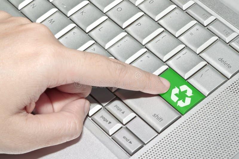 El presionado a mano en verde recicla el botón de la muestra fotografía de archivo