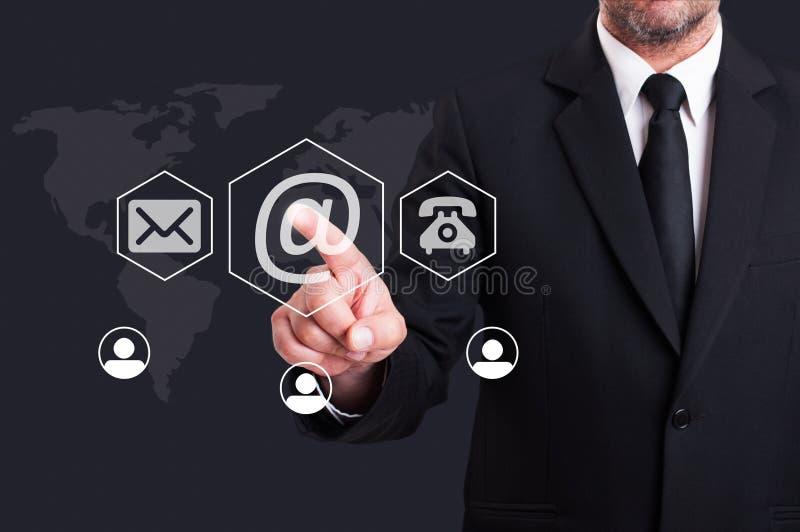 El presionar del hombre de negocios nos entra en contacto con usando el botón digital del correo electrónico imagen de archivo libre de regalías