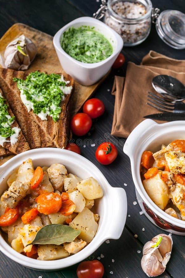 El primer coció la carne del pollo con las patatas y las zanahorias, bocadillo con queso y los tomates de cereza en un fondo de m fotos de archivo