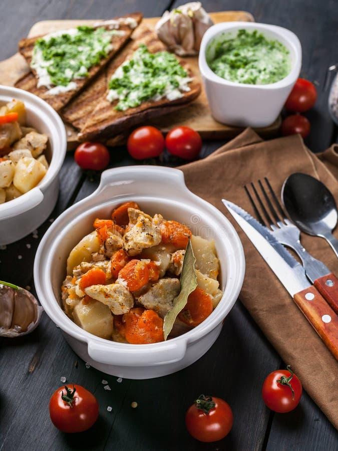 El primer coció el pollo con las patatas y las zanahorias, los bocadillos del queso y los tomates de cereza en un fondo de madera imágenes de archivo libres de regalías