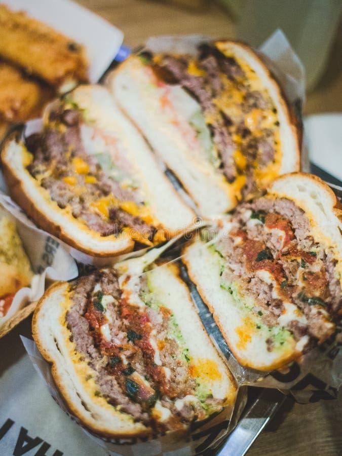 El primer cort? las hamburguesas de la carne pone en una bandeja en un caf? Hay inscripciones ilegibles en el paquete fotografía de archivo