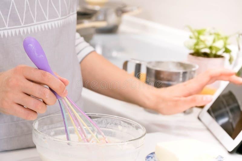 El primer da la señora que se coloca en cocina y que cocina la pasta Mirada de la tableta Femenino después de receta encendido foto de archivo