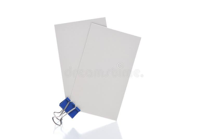 El primer de dos tarjetas de visita en blanco se sostuvo al lado de un clip de papel negro fotos de archivo