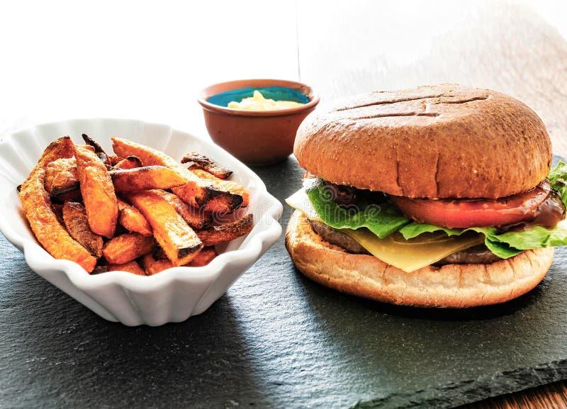 El primer de la hamburguesa hecha en casa deliciosa y de la patata dulce fríe en la bandeja de la pizarra imagenes de archivo