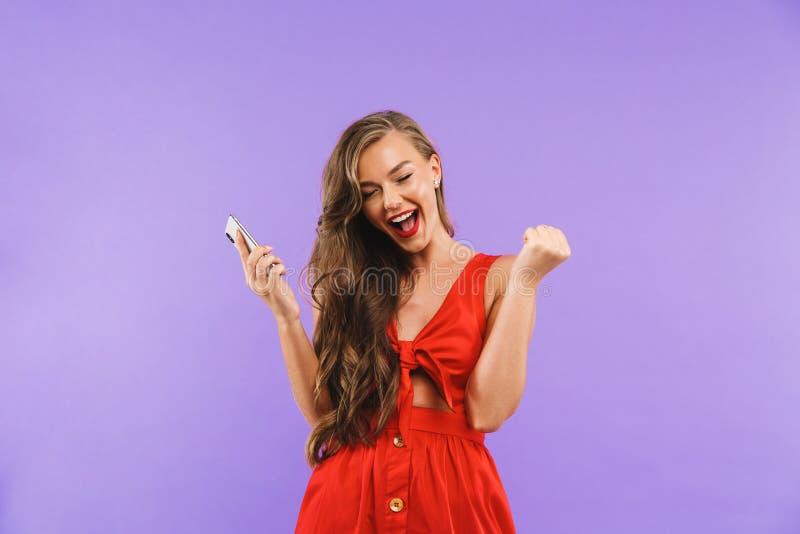 El primer de la imagen de la mujer joven alegre 20s que lleva el vestido rojo grita imagen de archivo libre de regalías
