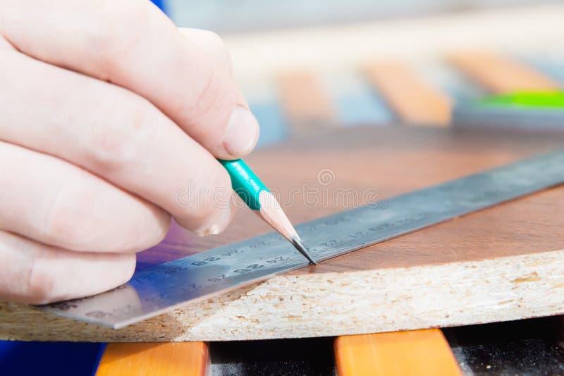 El primer de la mano del amo del ` s del carpintero se marca con una regla y un espacio en blanco del lápiz El concepto de manual imagen de archivo libre de regalías