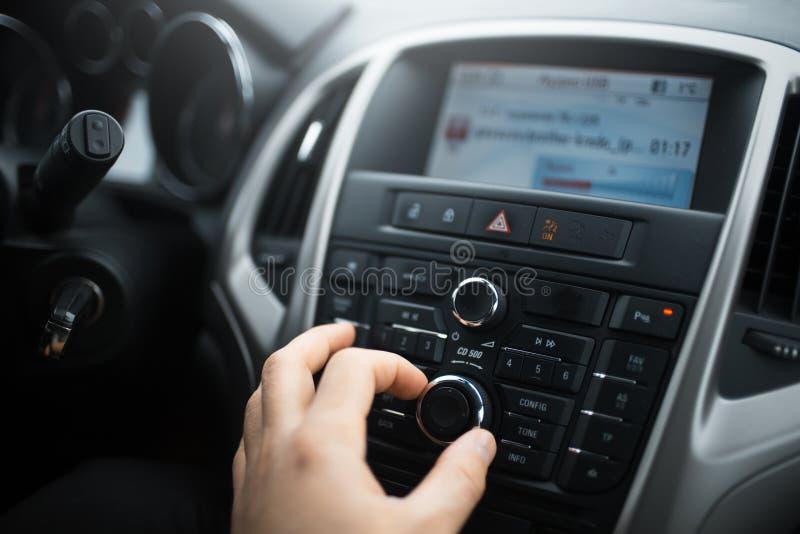 El primer de la mano del hombre ajusta el control de volumen del sistema de audio para el automóvil fotos de archivo