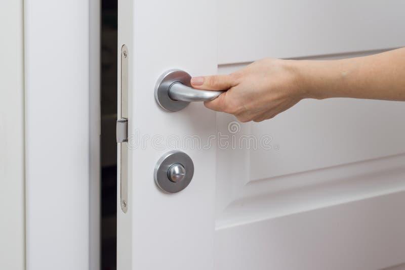 El primer de la mano femenina abre, cierra la puerta interior blanca imágenes de archivo libres de regalías