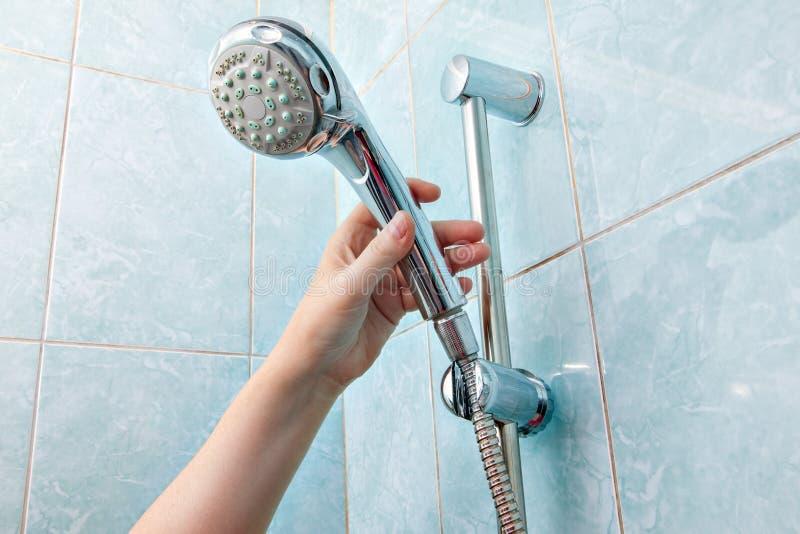 El primer de la mano humana ajusta la cabezal de ducha del tenedor con la manguera fotos de archivo libres de regalías