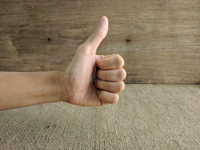 El primer de la mano masculina que muestra los pulgares sube la muestra imagen de archivo